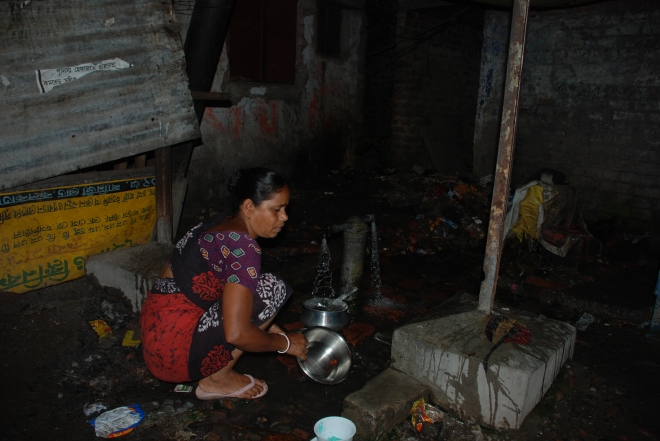 A women washes her vessels, using the free flowing water provided by the Kolkata Municipality